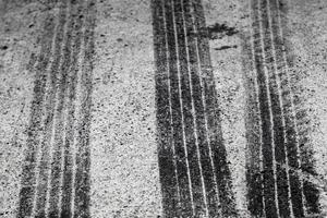 huellas de neumáticos negros en una carretera foto
