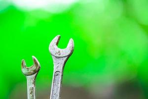 Two spanners on a green background