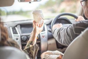 Una mujer sirviendo la taza de café caliente a su novio en el auto. foto