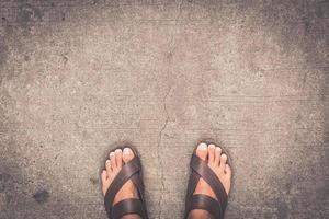 Los pies de un hombre con unas chanclas marrones de pie sobre el piso de concreto asfáltico