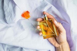persona sosteniendo una botella de perfume foto