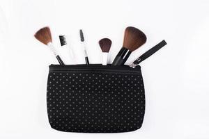 Pinceles de maquillaje en bolsa de cosméticos aislado sobre fondo blanco.