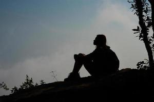 silueta de un excursionista sentado en la cima de la montaña con fondo de cielo azul foto