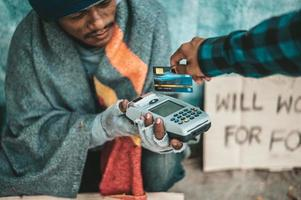 mendigos sentados debajo del paso elevado con una tarjeta de crédito y una máquina de deslizar tarjetas de crédito foto