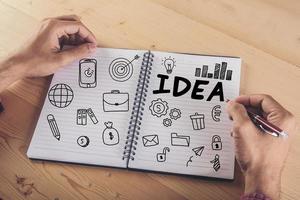 primer plano, de, hombre de negocios, escritura, en, cuaderno, con, garabato, icono foto