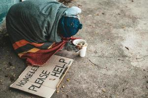 Beggars sitting on the street with homeless messages please help. photo