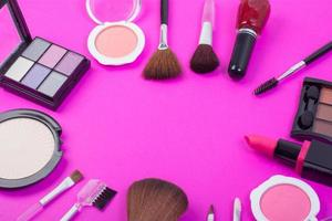 Top view of a collection of cosmetic beauty products on a pink background photo