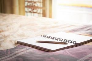 cuaderno y bolígrafo en la cama foto