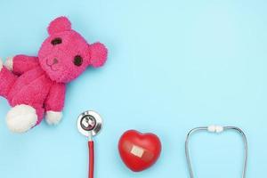 Estetoscopio y corazón rojo con osito de peluche sobre fondo azul.
