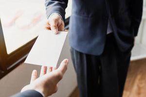 Person handing over a piece of paper photo