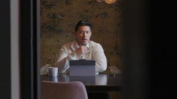 Asian young man sitting at table with laptop, having video-call.