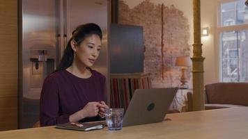 Mujer asiática sentada en la mesa de la cocina, con videollamada