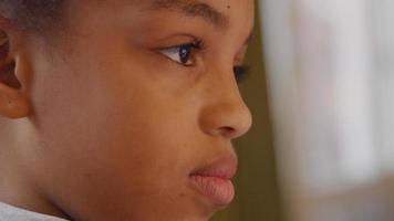 Close up of girl, eyes watching screen, eyebrows lifting, screen not shown
