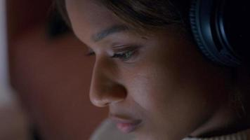 Close- up of black young woman, with headphone, head down, head moving softly