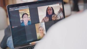 Close up of laptop screen with video call with three women in three frames shown. Laptop on lap of person who gestures.