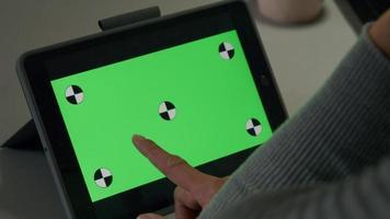 O dedo do jovem adulto asiático aponta e desliza sobre o tablet e segura o dispositivo com as duas mãos video