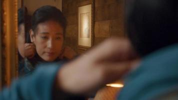 mulher se olha no espelho, enrola o lenço no pescoço, ajusta o cabelo, coloca máscara no rosto video