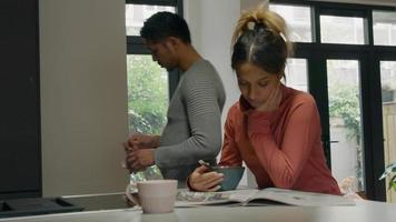 schwarze junge Frau sitzt an der Küchentheke, liest Zeitung, junger asiatischer Mann schließt sich ihr an und zeigt auf Zeitung