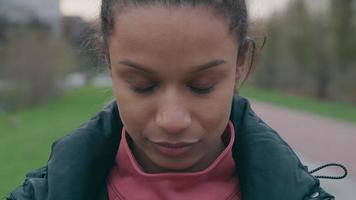 close-up de jovem negra, olhando para baixo, do lado de fora, coloca máscara facial, ajustando video