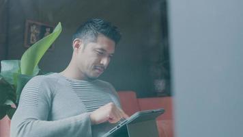 jovem asiático segura o tablet, olha, toca as mesas, para, inclina-se para trás video