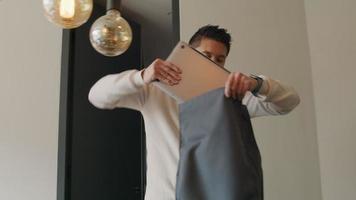 asiatischer junger Mann am Tisch, steckt Laptop und Notebook in den Rucksack, schließt ihn, schaut auf die Smartwatch, nimmt den Rucksack und geht video