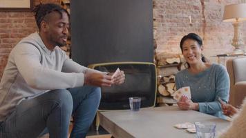duas mulheres, um homem e uma menina sentados ao redor da mesa, jogando cartas. o homem tira o cartão da pilha, olha para ele e o coloca em outra pilha. mulher e menina riem.