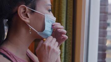 Asian woman looks through window, puts on face mask, adjusts it, turns and leaves