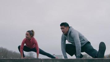 jovem asiático e negra no parque fazendo exercícios físicos, praticando alongamento da perna inteira, outro joelho dobrado