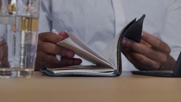 Nahaufnahme der Hände des reifen Mannes, Paging im Notizbuch, Stift haltend