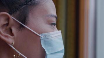 close-up de mulher asiática com máscara facial, olhando pela janela, perfil video
