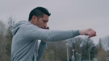 Joven asiático en el parque, haciendo ejercicio físico, movimientos de boxeo con brazos y puños frente a él, moviéndose y saltando