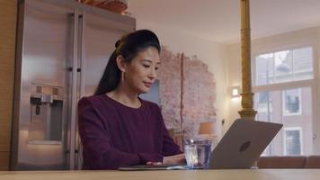 mulher asiática madura sentada à mesa na cozinha enquanto digita no laptop, olhando para cima duas vezes video