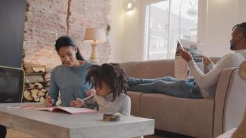 Girl and woman sit on floor, at low table. Man sits on sofa reading newspaper. Girl puts candy in her mouth, chewing. Woman puts cardigan on back of girl. Girl writes and reads in work book. Woman watches girl and homework, talking. Girl nods, woman l...