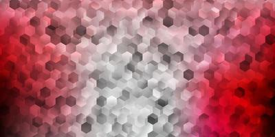 Light pink, red vector backdrop with a batch of hexagons.