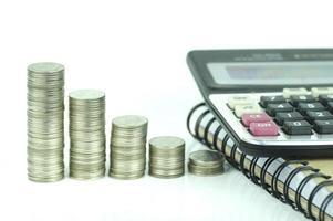 Monedas y calculadora sobre fondo blanco. foto