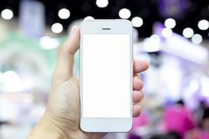 Holding white smart phone with bokeh lights background photo