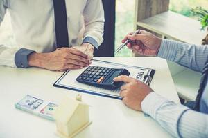 personas en una reunión con una calculadora. foto