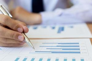 Using pen to mark up business charts photo