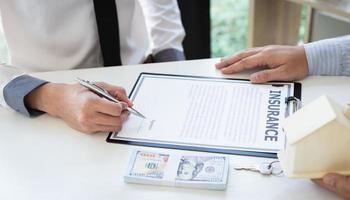 Person signing insurance document photo