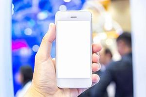 persona sosteniendo un teléfono inteligente blanco con pantalla en blanco
