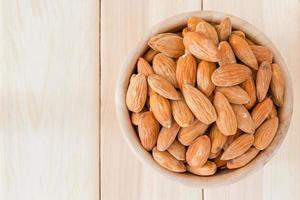 Almonds in wooden bowl on wooden table photo
