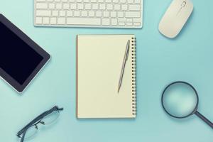 Vista superior del cuaderno vacío con herramienta de oficina sobre fondo azul suave