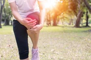 mujer tiene dolor de rodilla afuera foto