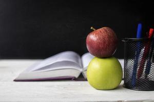 dos manzanas en un escritorio con cuaderno y bolígrafos foto