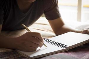 escribiendo en un cuaderno en la cama foto