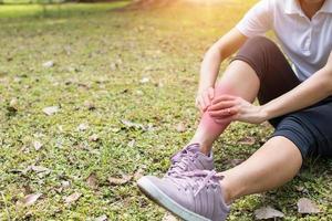mujer tiene dolor de pierna en el parque