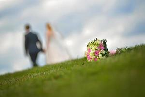 Wedding bouquet on grass with a married couple in the background