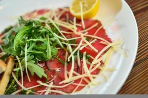 Beef carpaccio with parmesan cheese on a plate