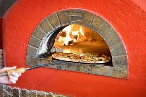 Pizza being pulled out of a pizza oven photo