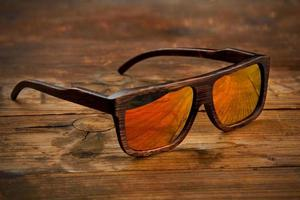 Dark-brown wooden sunglasses on wooden surface
